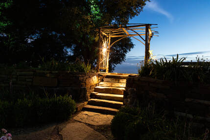 lighted stone walkway with arbor